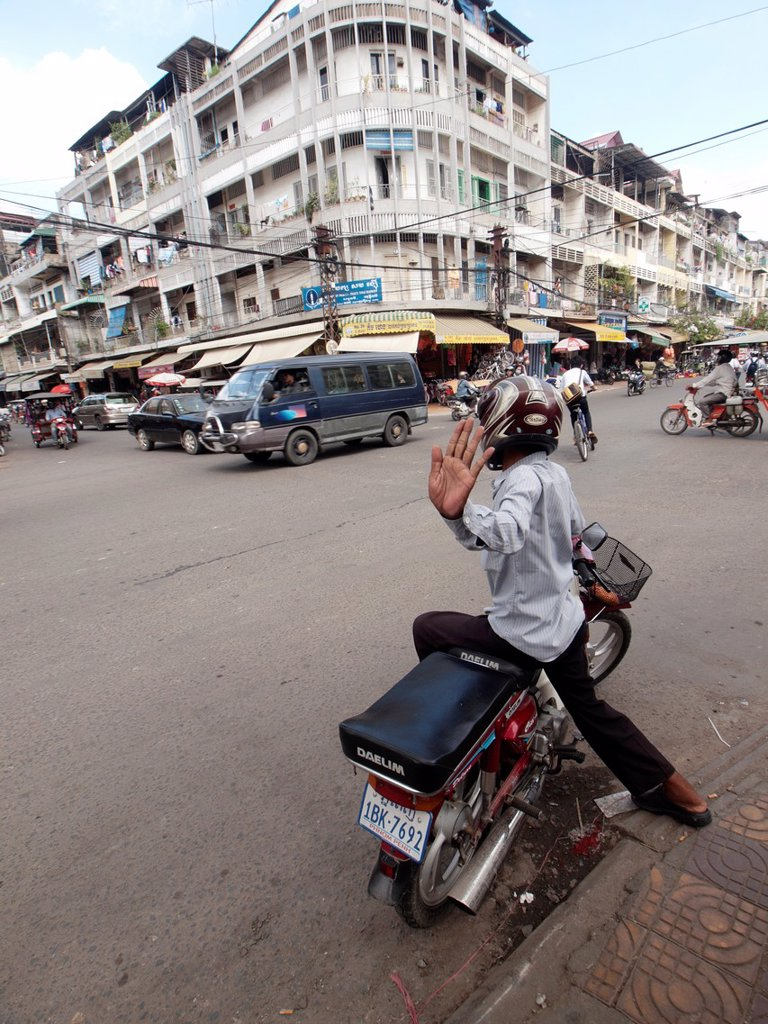 Stock Photo: 1566-1224394 Cambodian motorcycle parked at the intersection of a busy street in Phnom Penh Cambodia