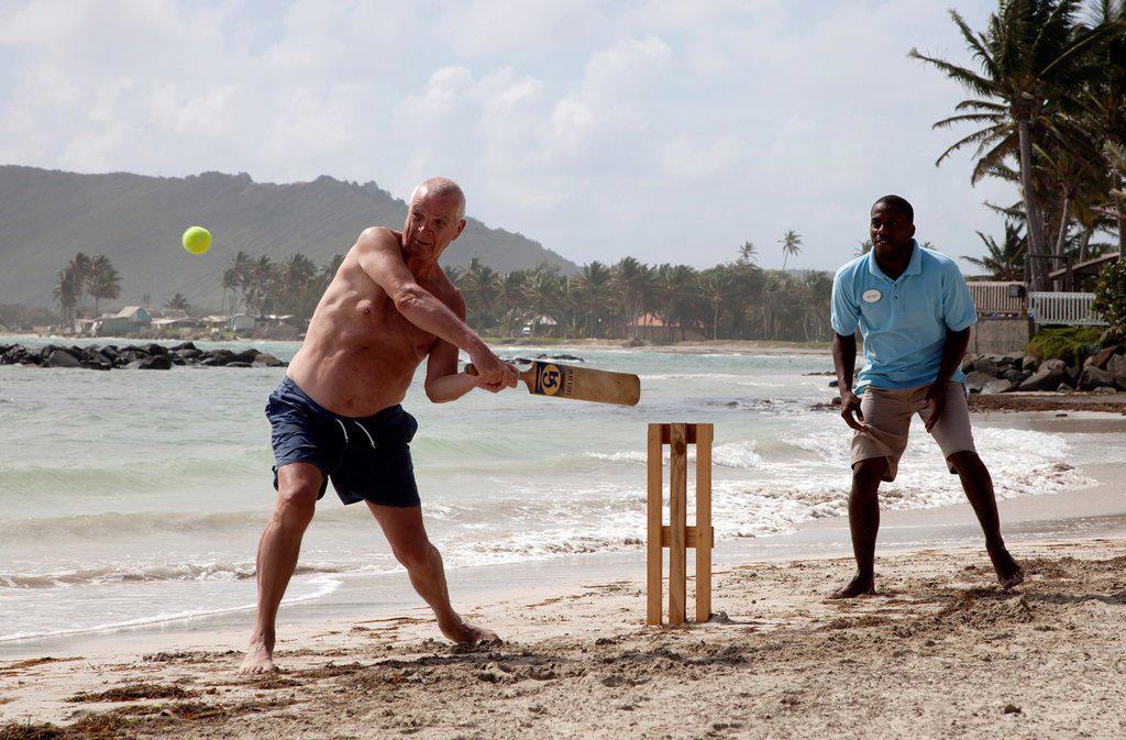 Tourist playing beach cricket, St Lucia, : Stock Photo