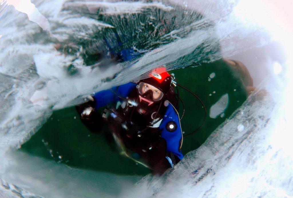 Diver looking through ice, Lake Baikal, Olkhon island, Siberia, Russia, Eurasia : Stock Photo