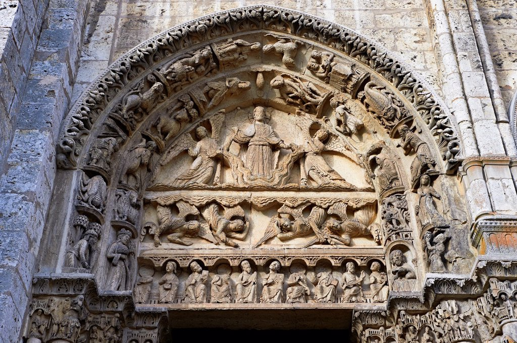 Stock Photo: 1566-1241761 West Facade, Left Portal - General View of Tympanum c  1145  Cathedral of Chartres, France  The tympanum of the left door shows the Ascension or the Second Coming  Christ crossed halo stands on a cloud, supported by two angels  Below are four angels descending from the clouds Some of them have their mouths open singing  On the lintel below are ten seated men holding books or scrolls and looking upward apostles  On the archivolts are the Signs of the Zodiac and the Labors of the Months   A UNESCO