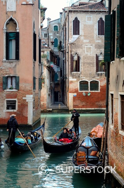 Stock Photo: 1566-1254186 Venetian channel photographed under sunlight with gondola passing by with tourists