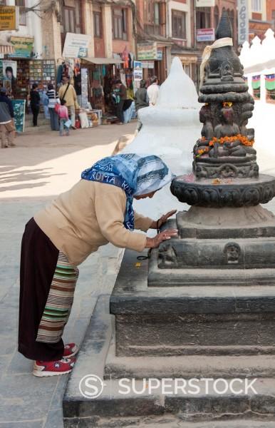 Bodhnath, Nepal. Worshiper Prays at a Shrine at the Base of the Bodhnath Stupa, a Tibetan Buddhist Stupa. : Stock Photo