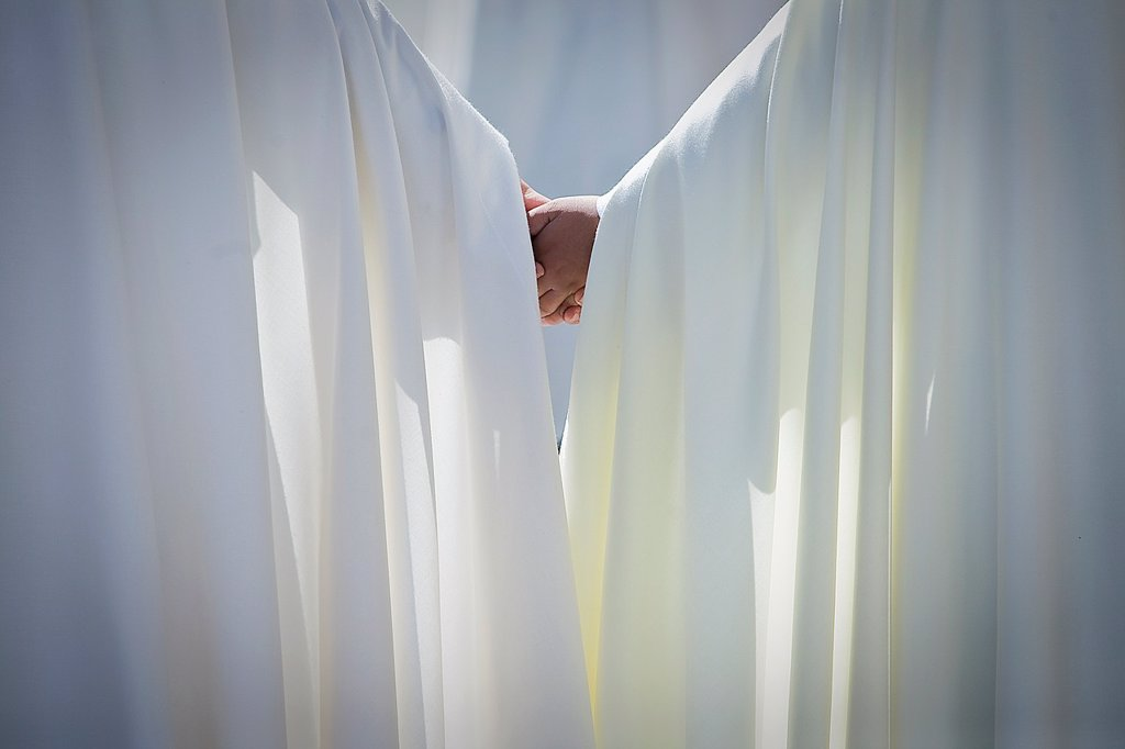 Stock Photo: 1566-1279100 Two penitents hand in hand in a Holy week procession, Spain.