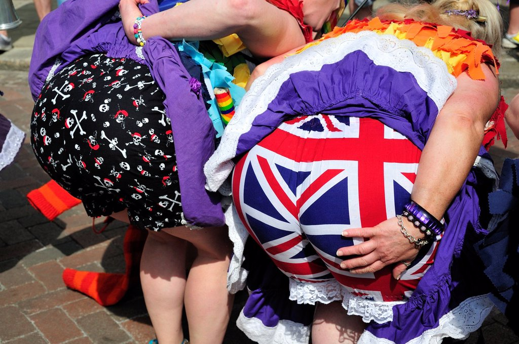 Stock Photo: 1566-1295326 Rochester, Kent, England, UK. Sweeps Festival, 2013. Two women dances bending over to reveal colourful bloomers.