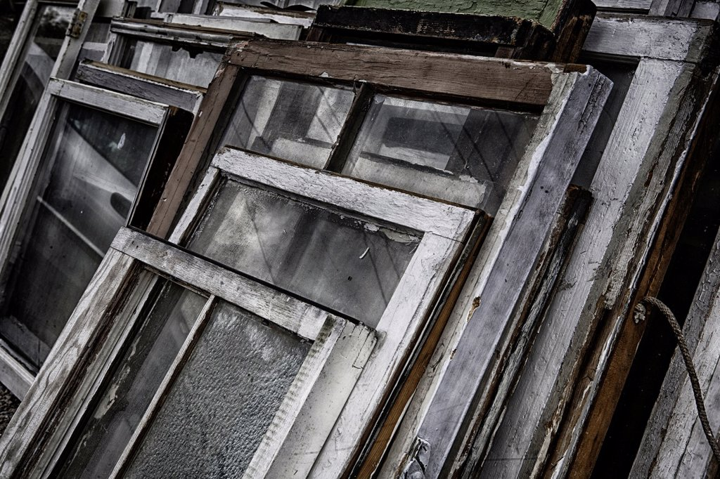 Stock Photo: 1566-1356072 Old, weathered, antique window frames stacked together outdoors at an antique store.
