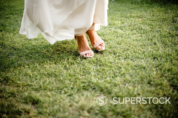 feet of bride on meadow : Stock Photo