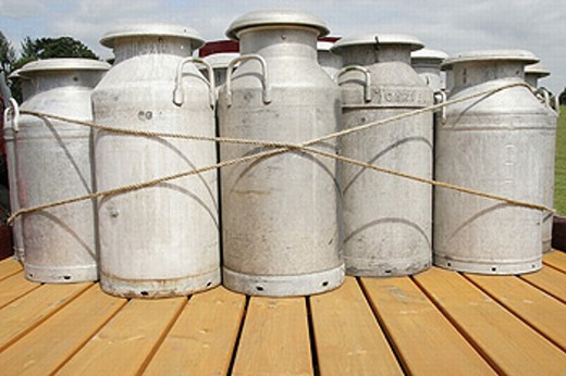 Milk churns of the back of a lorry : Stock Photo