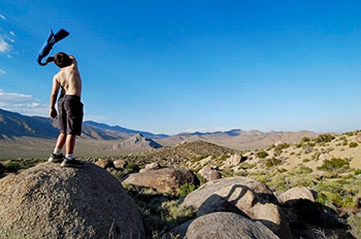 Stock Photo: 1566-248219 Preteen male waving with shirt. Death Valley. California. USA.