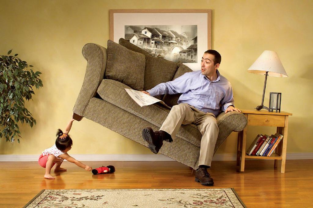 Girl lifting sofa. : Stock Photo