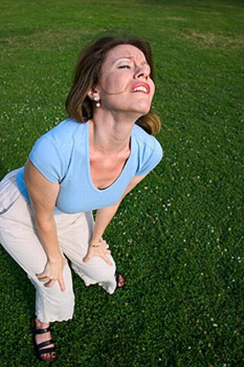 Young woman, standing on the grass at a park, dramatically expressing herself. : Stock Photo