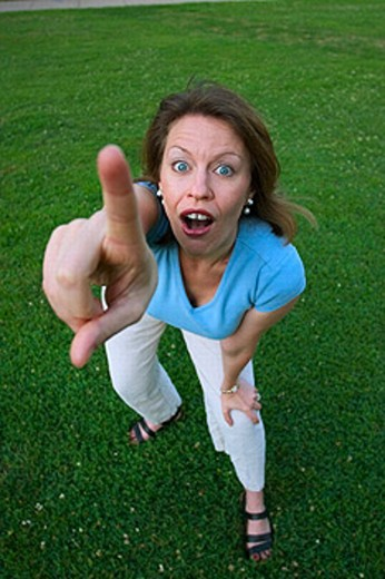 Young woman, standing on the grass at a park, dramatically pointing with her finger. : Stock Photo