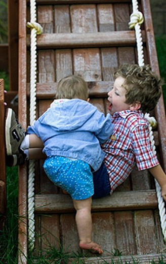 Baby and brother on ladder : Stock Photo