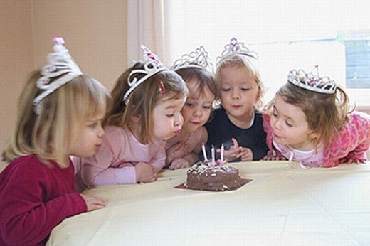 group of 3, year old girls at a party, blowing the candle out on a birthday cake : Stock Photo
