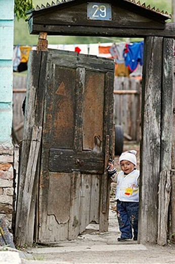 Stock Photo: 1566-253042 Happy child opening the gate of his yard - Tigmandru village, Mures County, Transylvania, Romania