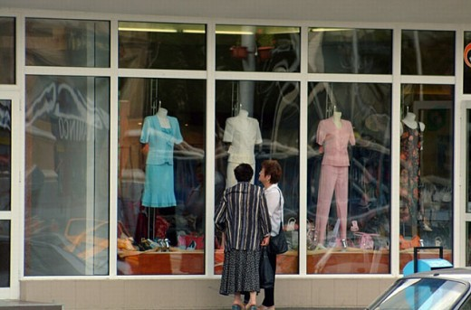 Two ladies are talking about a blue dress in front of a fashion store. Piatra Neamt, Romania, East Europe : Stock Photo