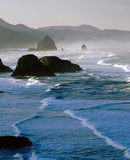 Stock Photo: 1566-257318 Sunset on the Pacific Ocean. Haystack Rock and the Needles. Oregon coast. Clatsop County. Cannon Beach. Oregon. USA.