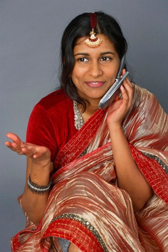 Indian woman in traditional clothing talking on cellular phone : Stock Photo