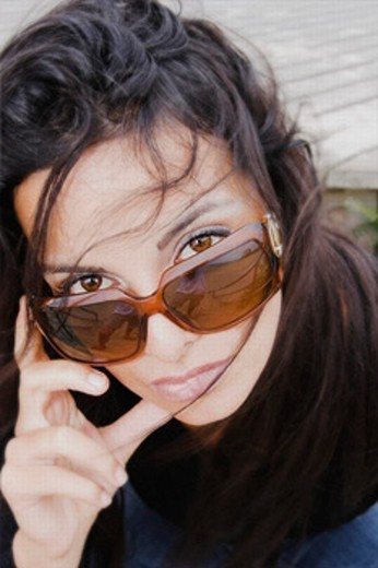 A young woman 20´s to 30´s with long dark hair a calm expression and wearing sunglasses looks into the camera : Stock Photo