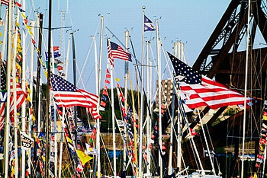 Flags from various yacht clubs are stung on the lines of sailboats about to enter a race on Lake Huron in Michigan. USA. : Stock Photo
