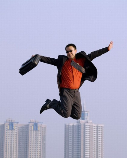 Young Asian (Chinese) businessman caught in mid-air, ground not visible, hi-rise buildings in the background : Stock Photo
