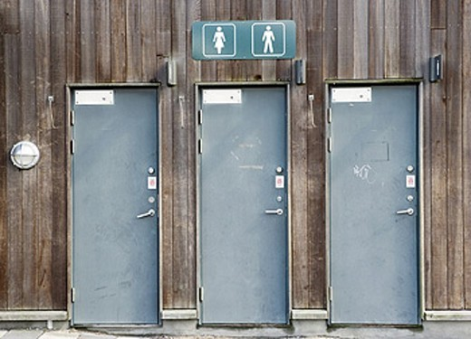 Signs for Men and Women´s toilets above three doors : Stock Photo