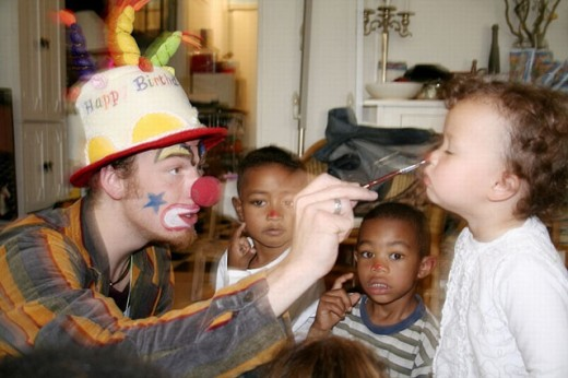 Clown doing face painting on birthday party : Stock Photo