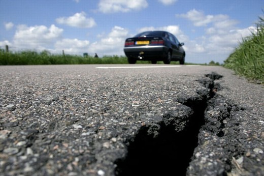 Broken asphalt road and car : Stock Photo