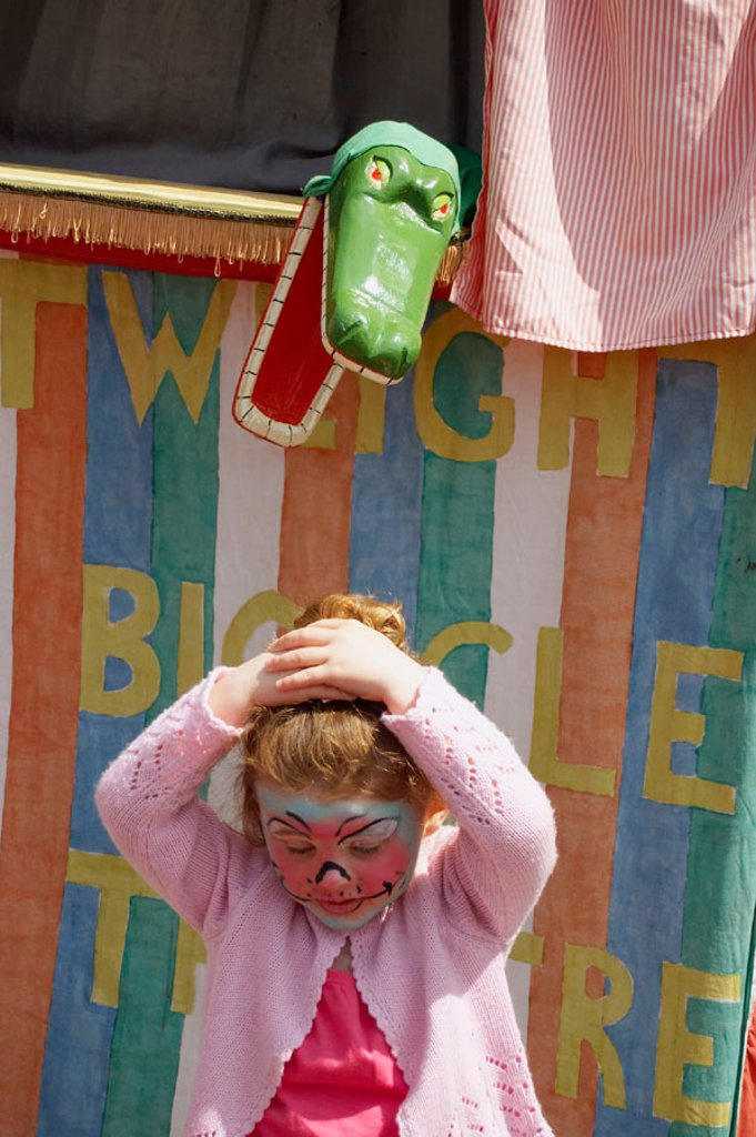 Stock Photo: 1566-269726 3 year old girl standing in front of a Punch and Judy stall, with a crocodile snapping at her head.