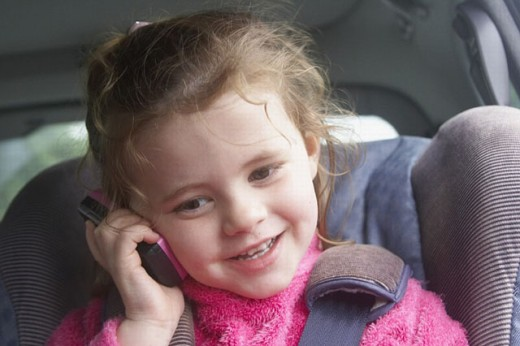Stock Photo: 1566-269850 3 year old girl smiling as she talks into a mobile phone in her carseat