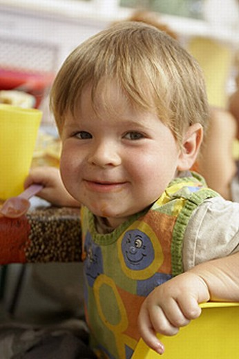 Stock Photo: 1566-270065 2 year old boy sitting at nursery, grinning into camera.