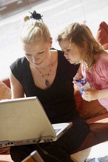 Stock Photo: 1566-270079 21 year old girl working on a laptop on her knee, with a 3 year old girl watching