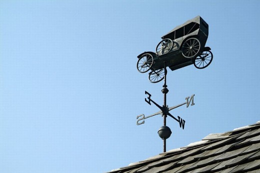 Weather vane in the shape of an antique automobile car shows the direction of the wind : Stock Photo