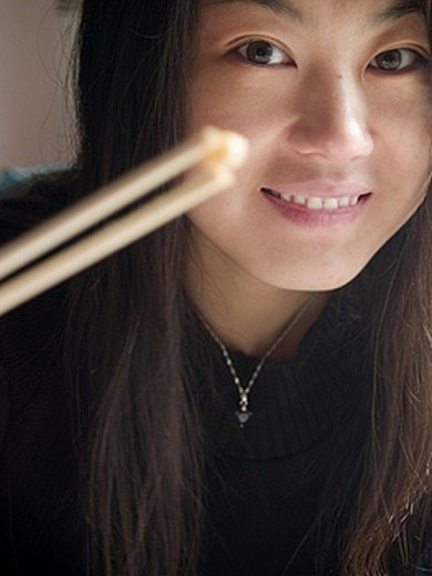 Stock Photo: 1566-271689 Good looking Chinese girl in black holding a seed of corn with chopsticks