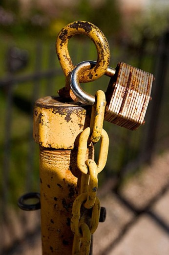 Stock Photo: 1566-272694 Rusted lock holding a chain to a post near a fence.