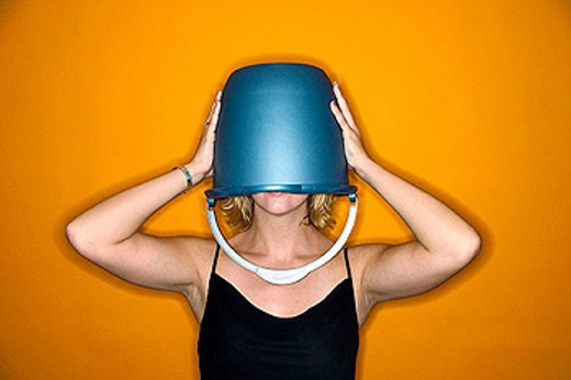 Young blond woman wearing a blue bucket on her head that covers her eyes : Stock Photo
