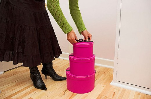 Stock Photo: 1566-274907 Stack of three pink gift boxes on a wooden floor.