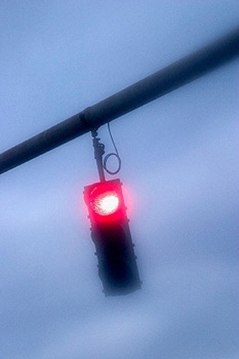 Traffic light, on red, hanging over a city street : Stock Photo