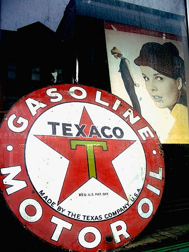 Stock Photo: 1566-286398 A vintage Texaco filling station sigh and a vintage magazine cover poster are caputred through the window of an antique shop.