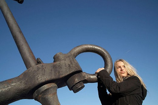 Stock Photo: 1566-290468 Attractive blond girl holding ship´s anchor isolated against blue sky