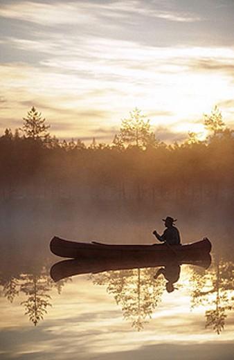Stock Photo: 1566-290882 A man paddle a canoe a misty summermorning at sunrise. Byske. Vasterbotten. Sweden.