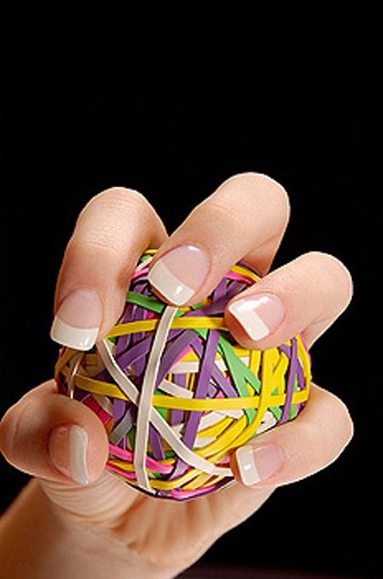 Manicured female had with long fingernails, gripping a rubberband ball as if squeezing or pitching a ball.  Black backround.  Room for text/ copy.  Fingernails appear strong and are pained with clear, shiny polish. : Stock Photo