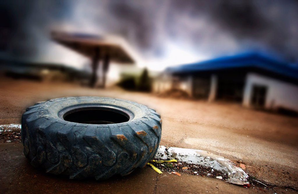 Abandoned gas station with truck tire : Stock Photo