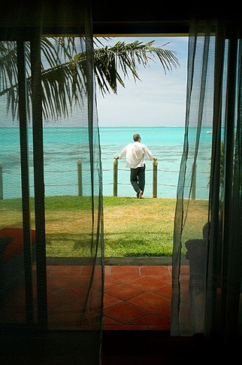 Stock Photo: 1566-297918 Man overlooking tropical turquoise lagoon out the front of his luxury resort bungalow.