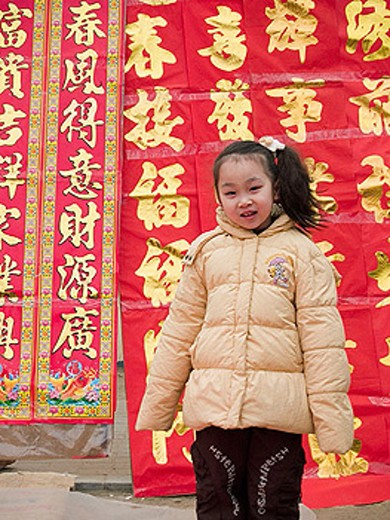 Stock Photo: 1566-300036 Little girl playing in front of Chinese scrolls