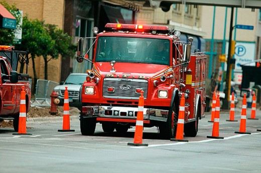 Stock Photo: 1566-301511 Fire truck navigates through construction zone markers during emergency run on city streets.
