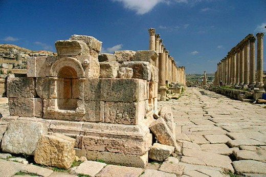 Row of columns and tetrapylon at fore, archaeological site of Jerash. Jordan : Stock Photo