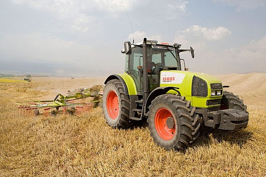 Agricultural machinery. Windrower. Harvesting of cereals,  ´Learza´ estate. Near Estella, Navarre, Spain : Stock Photo