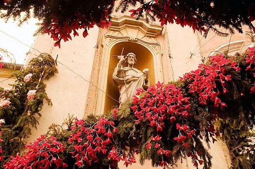 Festivity of Holy Cross (Festa della Santa Croce), decoration with the traditional handmade flowers of paper near the  Parish Church. Carzano, Trento province, Italy. : Stock Photo