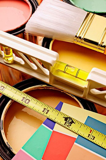 Cans of paint with level, tape measuring tape and paint swatches : Stock Photo