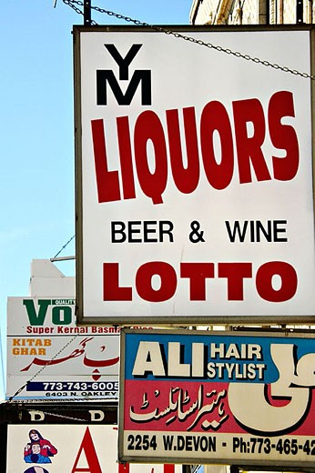 Signs for stores along Devon Avenue, multiethnic shopping district, hair stylist, liquor. Chicago. Illinois, USA : Stock Photo